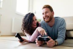 Счастливые пары играя видеоигры дома Стоковые Изображения RF