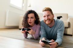 Счастливые пары играя видеоигры дома Стоковые Фото