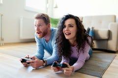 Счастливые пары играя видеоигры дома Стоковая Фотография RF