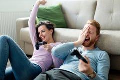 Счастливые пары играя видеоигры дома Стоковое Фото