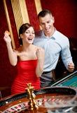 Счастливые пары играя выигрыши рулетки стоковое изображение rf