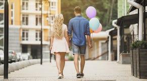 Счастливые пары идя вниз с улицы города, держа красочные воздушные шары, романтичная дата Стоковое Изображение