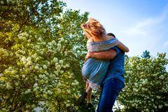Счастливые пары имея потеху в зацветая саде Человек держит его подругу в руках и закручивает на заход солнца Парни наслаждаясь жи Стоковое Фото