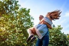 Счастливые пары имея потеху в зацветая саде Человек держит его подругу в руках и закручивает на заход солнца Парни наслаждаясь жи Стоковое фото RF