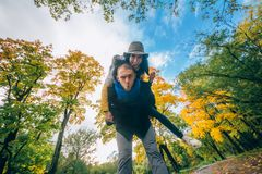 Счастливые пары имея потеху в парке осени Желтые деревья и листья Смеясь над человек и женщина внешние черная изолированная свобо Стоковые Фото