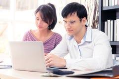 Счастливые пары используя компьютер работая совместно дома Стоковая Фотография RF