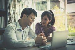 Счастливые пары используя компьютер работая совместно дома Стоковые Фото