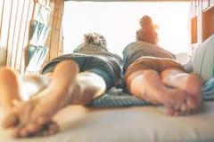 Счастливые пары лежа на кровати внутри минифургона смотря заход солнца - людей перемещения имея нежные моменты во время поездки стоковое фото rf