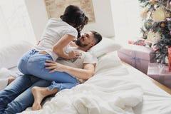 Счастливые пары любовников лежат на кровати и целовать Интерьер рождества Любовники совместно стоковое фото rf