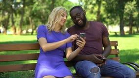 Счастливые пары наблюдая смешные видео в сети на смартфоне, смеясь совместно сток-видео