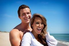 Счастливые пары на пляже стоковые изображения
