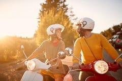 Счастливые пары на скутере наслаждаясь поездкой на каникулах на заходе солнца стоковое изображение rf