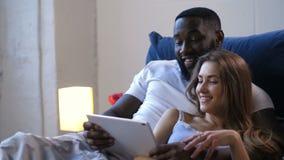 Счастливые пары обнимая лежать в кровати с сенсорной панелью сток-видео