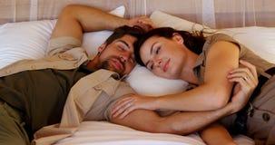 Счастливые пары отдыхая на кровати на каникулах 4k акции видеоматериалы
