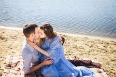 Счастливые пары отдыхая на пляже Стоковые Изображения