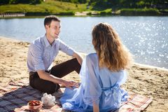 Счастливые пары отдыхая на пляже Стоковое Изображение