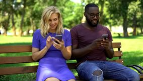 Счастливые пары поглощенные социальными средствами массовой информации используя смартфоны вместо взаимодействовать стоковое фото