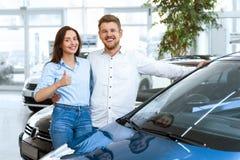 Счастливые пары покупая автомобиль совместно стоковое фото