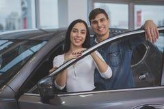 Счастливые пары покупая новый автомобиль на салоне дилерских полномочий стоковые фотографии rf