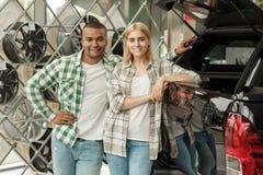 Счастливые пары покупая новый автомобиль совместно на дилерских полномочиях стоковое изображение