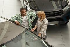 Счастливые пары покупая новый автомобиль совместно на дилерских полномочиях стоковое изображение rf
