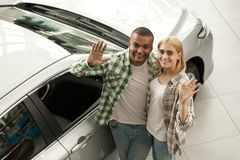 Счастливые пары покупая новый автомобиль совместно на дилерских полномочиях стоковое фото