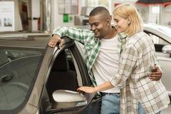 Счастливые пары покупая новый автомобиль совместно на дилерских полномочиях стоковая фотография