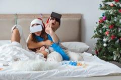 Счастливые пары празднуя праздник рождества в кровати Стоковая Фотография