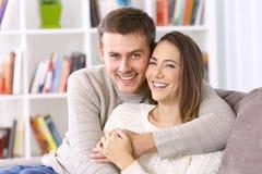 Счастливые пары представляя совместно на кресле дома Стоковое Фото