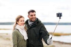 Счастливые пары принимая selfie на пляже в осени стоковое изображение