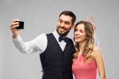 Счастливые пары принимая selfie смартфоном стоковая фотография rf