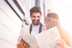 Счастливые пары при карта выбирая первое назначение стоковое фото