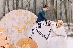 Счастливые пары свадьбы мягко держа руки на больших винтажных часах в украшениях леса осени творческих Стоковые Изображения