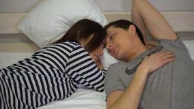 Счастливые пары семьи дома лежа на кровати и говорить сток-видео