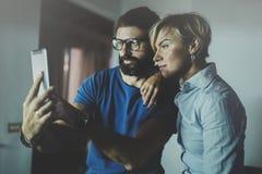 Счастливые пары семьи используя smartphone в гостиной дома Бородатый человек в стеклах глаза делая selfie с молодой блондинкой Стоковые Изображения