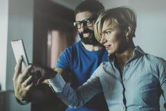 Счастливые пары семьи используя smartphone в гостиной дома Бородатый человек в стеклах глаза делая selfie с молодой блондинкой Стоковая Фотография RF