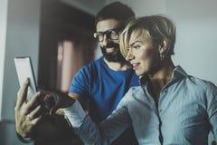 Счастливые пары семьи используя smartphone в гостиной дома Бородатый человек в стеклах глаза делая selfie с молодой блондинкой Стоковые Изображения RF
