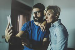 Счастливые пары семьи используя smartphone в гостиной дома Бородатый человек в стеклах глаза делая selfie с молодой блондинкой Стоковое Изображение RF