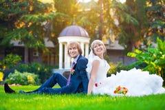 Счастливые пары сидят на зеленой траве Стоковое Изображение RF