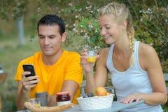Счастливые пары сидя в человеке кафа улицы используя телефон Стоковые Фото