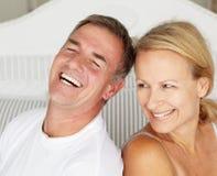 Счастливые пары сидя назад для поддержки на кровати стоковая фотография