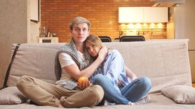 Счастливые пары сидя на кресле смотря ТВ совместно дома в живущей комнате видеоматериал