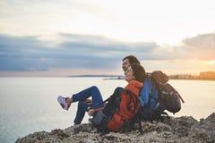 Счастливые пары сидя на утесе и смотря заход солнца Стоковые Фотографии RF