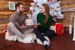 Счастливые пары сидя под рождественской елкой и давая подарочные коробки indoors стоковое фото rf