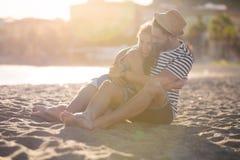 Счастливые пары сидя совместно на пляже обнимая один другого Стоковая Фотография
