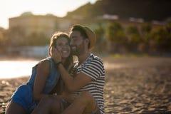Счастливые пары сидя совместно на смеяться над пляжа Стоковые Изображения RF