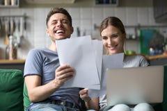 Счастливые пары смеясь над имеющ потеху с документами и компьтер-книжкой стоковые фотографии rf