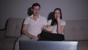 Счастливые пары смотря кино на ТВ сидя на кресле дома видеоматериал
