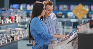 Счастливые пары смотря новую цифровую фотокамеру на магазине электроники сток-видео