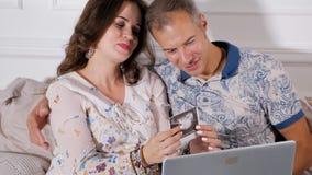 Счастливые пары смотря развертку младенца сток-видео